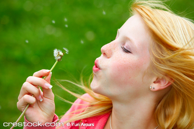 Young teenager blowing a dandelion. Make a wish